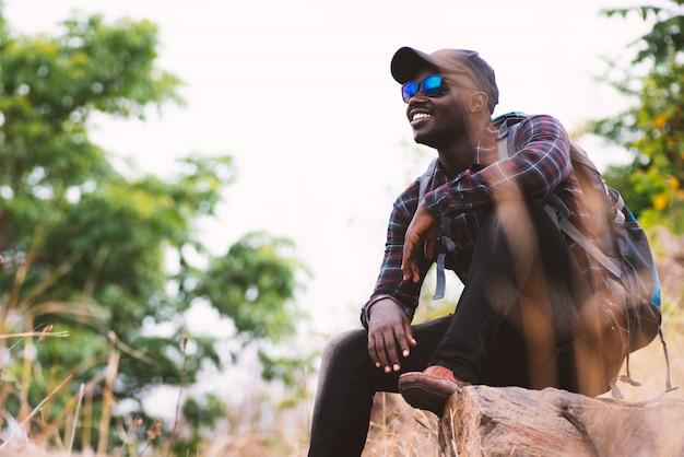 Afrikanischer mannreisender, der oben auf berg mit rucksack sitzt