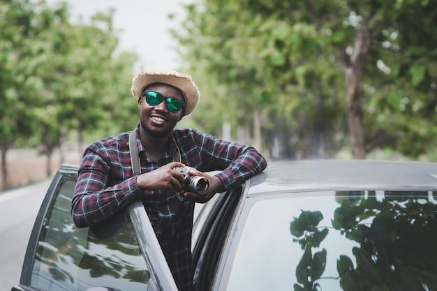 Afrikanischer mannreisender, der sonnenbrille trägt und kamera mit seinem auto hält