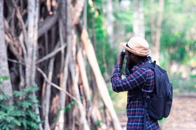 Afrikanischer mannreisenderforscher mit fotokamera im wald.