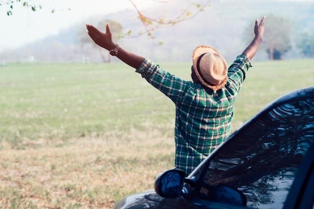 Afrikanischer mannreisendhippie, der auf dem auto schaut und sitzt