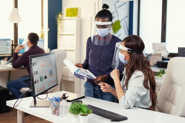 Afrikanischer marketingspezialist, der dem mitarbeiter am arbeitsplatz das projekt mit gesichtsmaske gegen covid19 erklärt. diverses team, das während der globalen pandemie mit coronavirus die soziale distanzierung respektiert. n