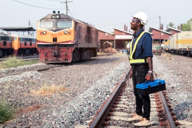 Afrikanischer maschinenbautechniker, der einen helm, haine und eine sicherheitsweste trägt, benutzt einen schraubenschlüssel, um den zug zu reparieren
