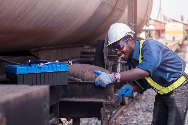 Afrikanischer maschinenbautechniker, der einen helm, haine und eine sicherheitsweste trägt, verwendet einen schraubenschlüssel, um das zugtransportgas und -öl zu reparieren