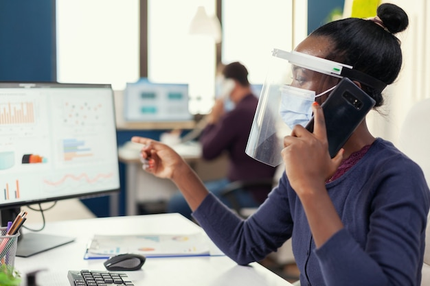 Afrikanischer mitarbeiter, der im büro auf dem smartphone spricht und eine gesichtsmaske gegen coronavirus trägt
