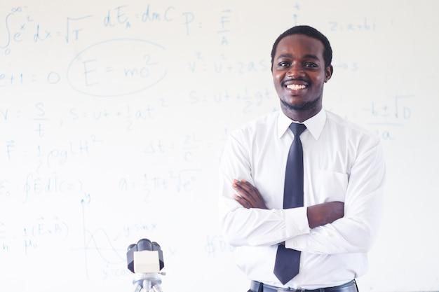 Afrikanischer naturlehrer, der in der stammklasse mit mikroskop unterrichtet und lächelt.
