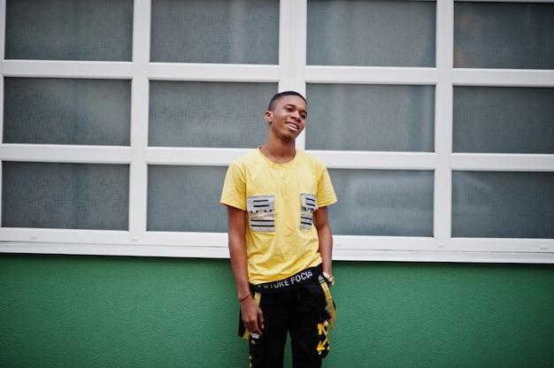 Afrikanischer nigerianischer mann stellte draußen gegen grüne und weiße wand auf
