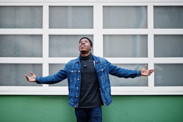 Afrikanischer nigerianischer mann stellte im freien angehobene hände gegen grüne und weiße wand auf