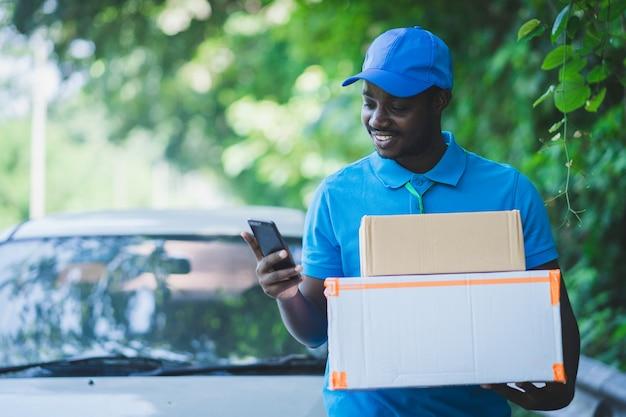 Afrikanischer postzustellungskuriermann, der smartphone und lieferpaket verwendet