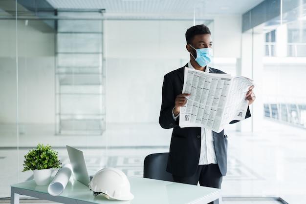 Afrikanischer schöner geschäftsmann in der medizinischen maske, die die zeitung am bürogebäude liest