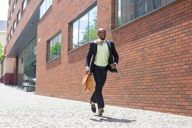 Afrikanischer schwarzer junger geschäftsmann, der in einer stadtstraße läuft