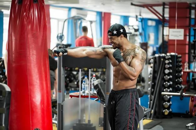 Afrikanischer schwarzer männlicher boxer-schlagball, der boxhandschuhe im fitnessstudio trägt