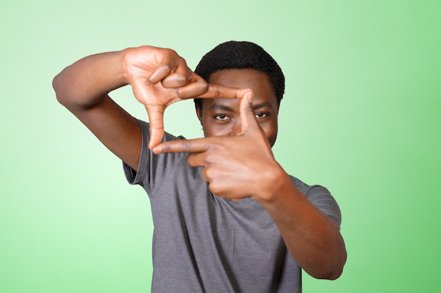 Afrikanischer schwarzer mann, der feldzeichen mit seinen händen bildet