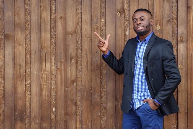 Afrikanischer schwarzer mann mit bart, der mit dem finger auf holzhintergrund, exemplar zur seite zeigt. er lächelt und schaut in die kamera.