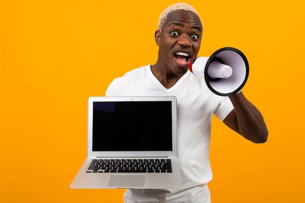 Afrikanischer schwarzer mann mit megaphon und laptop auf gelb