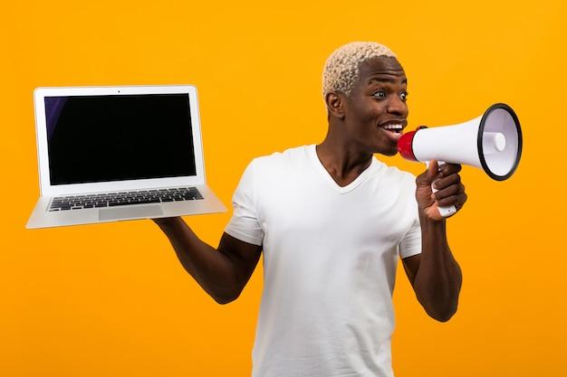 Afrikanischer schwarzer mann mit weißen haaren spricht in einem megaphon, der einen laptop auf gelb hält