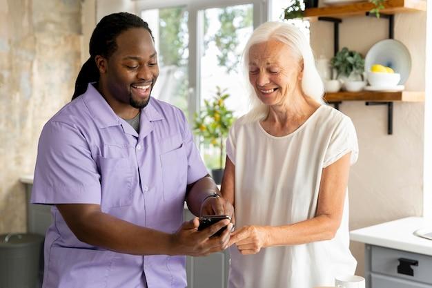 Afrikanischer sozialarbeiter, der einer älteren frau hilft