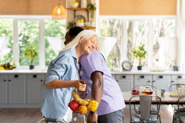 Afrikanischer sozialarbeiter kümmert sich um eine ältere frau