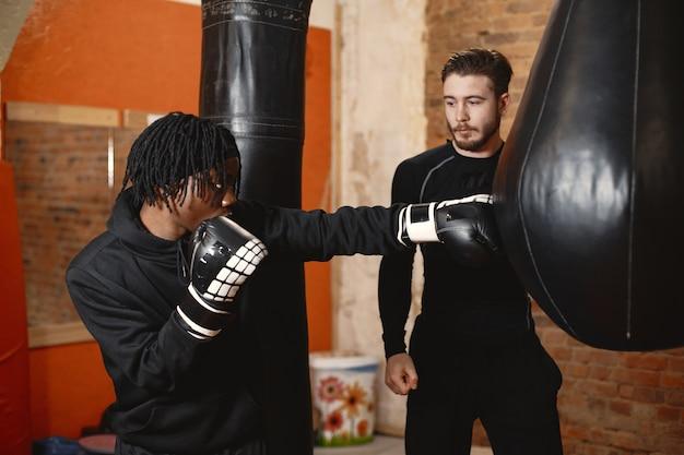 Afrikanischer sportlicher mann, der boxt. training für gemischte leute.