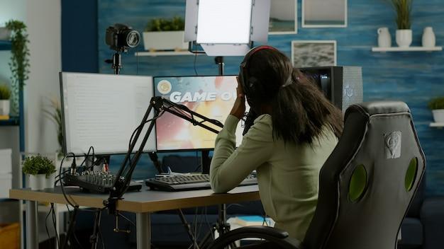 Afrikanischer streamer bedauert den verlust eines live-weltraum-shooter-spielturniers, das den tempel berührt und mit dem team plaudert. professioneller gamer, der online-videospiele mit neuer grafik auf einem leistungsstarken computer streamt.
