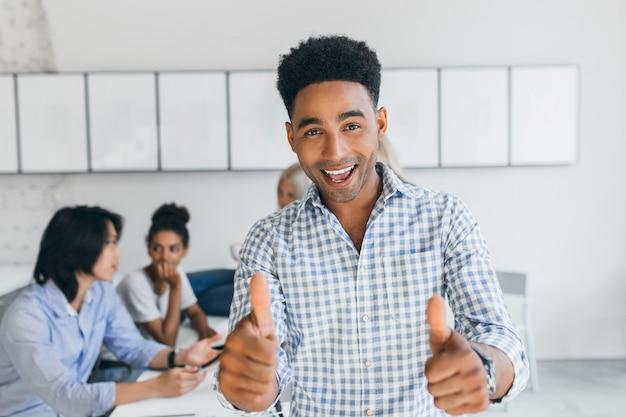 Afrikanischer student hat prüfungen bestanden und spaß mit universitätskameraden gehabt. internationale büroangestellte diskutieren über neue unternehmensziele.