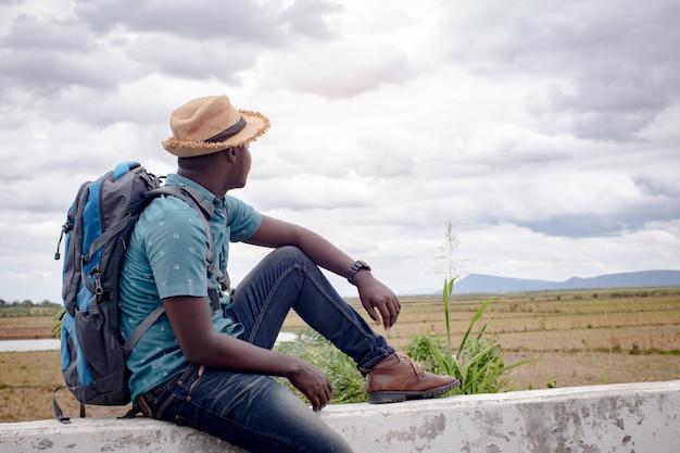 Afrikanischer touristischer reisendmann mit rucksack auf ansicht des berges