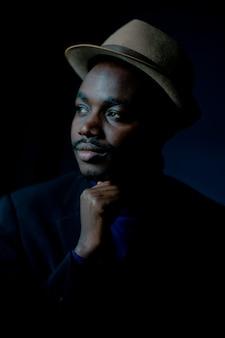 Afrikanischer trauriger mann, der im dunklen raum sitzt, zurückhaltender stil