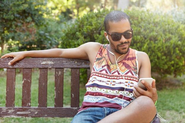 Afrikanischer typ in kopfhörern, der auf bank im stadtpark sitzt, musik auf seinem smartphone hört, e-mails mit einem internetfähigen mobiltelefon abruft, beiträge mag und kommentare in sozialen netzwerken hinterlässt