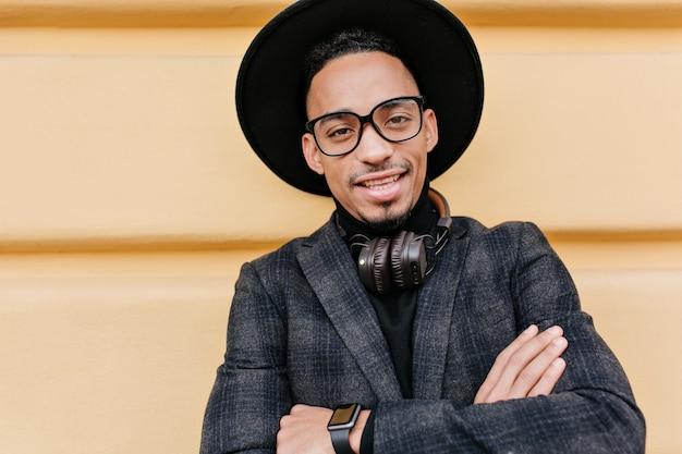 Afrikanischer typ trägt trendige armbanduhr, die mit lächeln nahe beiger wand aufwirft. außenporträt des schwarzen mannes in guter laune stehend mit verschränkten armen.