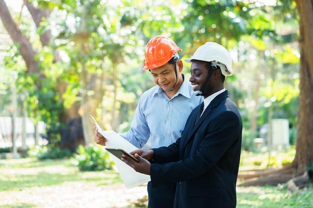 Afrikanischer und asiatischer expertenteamplan des architekteningenieurs zwei mit lächeln in der grünen natur.