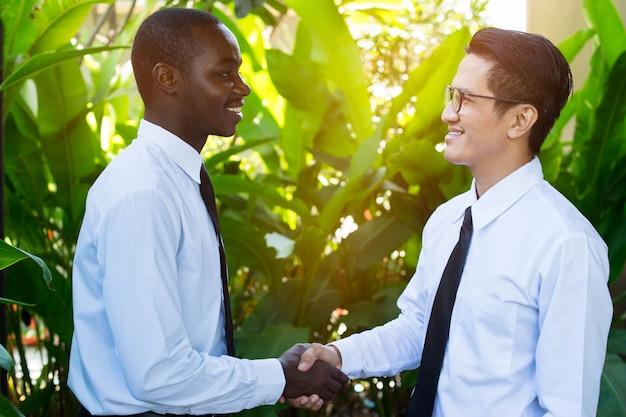 Afrikanischer und asiatischer geschäftsmann, der hand mit glücklichem und lächeln rüttelt.