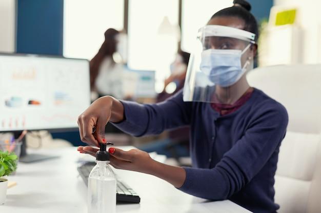 Afrikanischer unternehmer, der am arbeitsplatz händedesinfektionsmittel mit gesichtsmaske verwendet. geschäftsfrau am neuen normalen arbeitsplatz desinfiziert, während kollegen im hintergrund arbeiten.