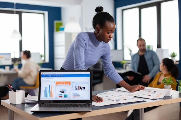Afrikanischer unternehmer eines start-up-unternehmens, das diagramme auf dokumentenpapieren liest. diverses team von geschäftsleuten, die finanzberichte des unternehmens vom computer analysieren. erfolgreicher unternehmensprofi