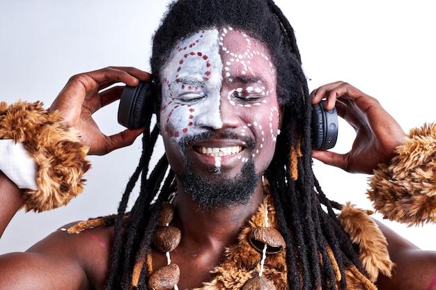 Afrikanischer ureinwohner in ethnischer kleidung genießen musik in kopfhörern, isoliert über weißer wand, stehend mit geschlossenen augen