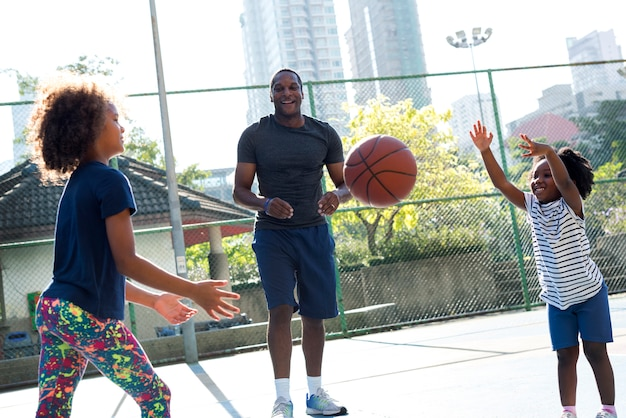 Afrikanischer vater, der zeit verbringt, basketball zu spielen