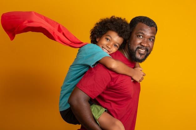 Afrikanischer vater und sohn spielen tagsüber superhelden. leute, die spaß gelbe wand haben. konzept der freundlichen familie.