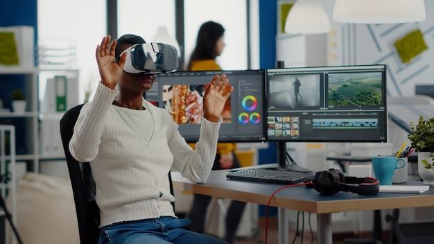 Afrikanischer videoeditor, der eine vr-brille erlebt, die gestikuliert, die videofilmmontage bearbeitet, ...