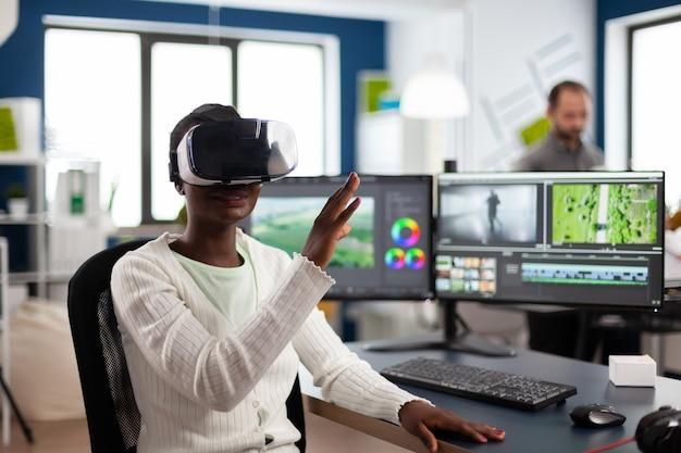 Afrikanischer videoeditor, der vr-brillen erlebt, gestikuliert, videofilmmontagen bearbeitet und mit filmmaterial und ton auf einem computer mit zwei displays arbeitet