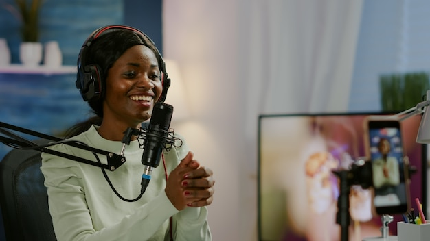 Afrikanischer vlogger, der videoblog mit smartphone mit moderner ausrüstung im heimstudio-podcast aufzeichnet. medienstar, der für die übertragung in die kamera schaut und spaß daran hat, technologie zu verwenden, um mit dem publikum in kontakt zu treten