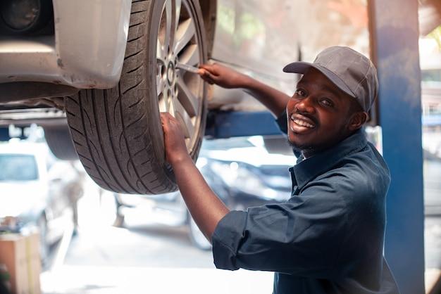 Afrikanischer wartungsmann, der reifenservice über versicherungssystem an der garage mit lächeln überprüft