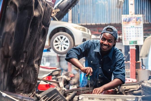 Afrikanischer wartungsmann, der reifenservice über versicherungssystem in der garage mit lächeln und glücklich prüft