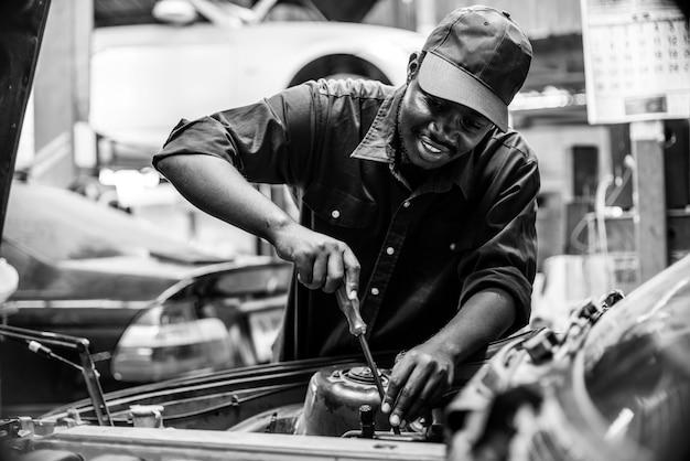 Afrikanischer wartungsmann, der reifenservice über versicherungssystem in der garage prüft. schwarzer und weißer stil