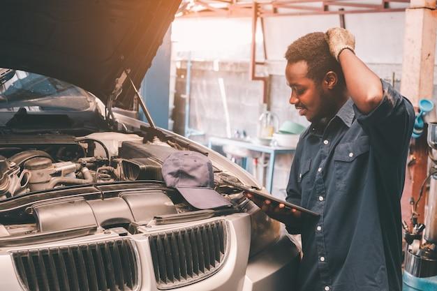 Afrikanischer wartungsmann hat probleme, wenn er das auto überprüft, das versicherungssystem bei der autoreparatur und das prüfzentrum bedient