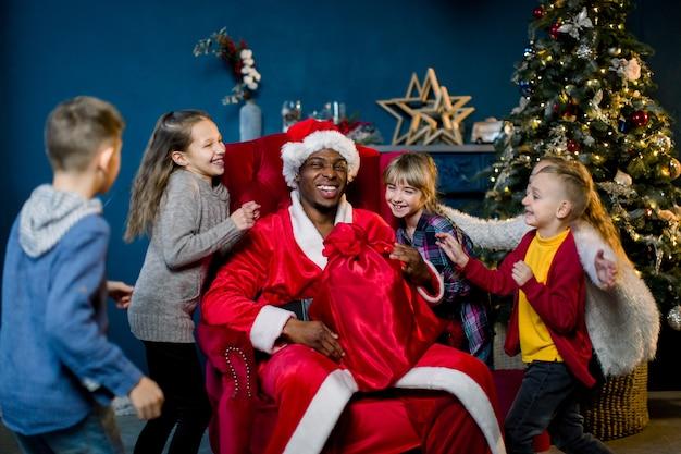 Afrikanischer weihnachtsmann und glückliche kinder auf dem hintergrund des weihnachtsbaumes