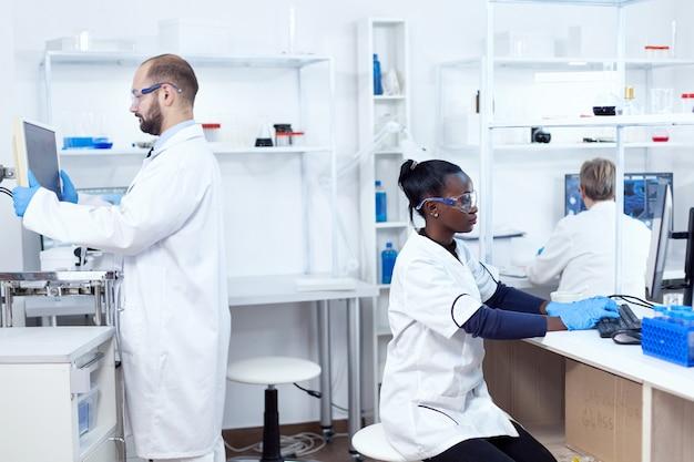 Afrikanischer wissenschaftler, der an computer mit schutzausrüstung arbeitet und analysen durchführt. multiethnisches forscherteam, das an einer mikrobiologischen labortestlösung für medizinische zwecke arbeitet.
