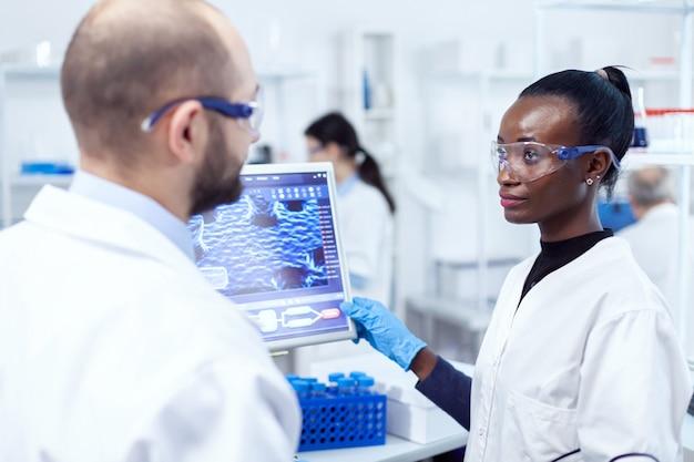 Afrikanischer wissenschaftler, der das ergebnis der virusforschung mit dem vorgesetzten im labor unter verwendung des computers bespricht. multiethnisches team medizinischer forscher, die im sterilen labor mit schutzbrillen zusammenarbeiten