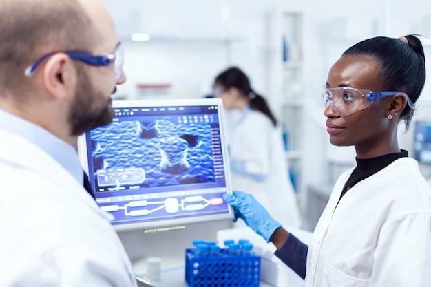Afrikanischer wissenschaftler, der mit hilfe eines kollegen ein chemieexperiment mit computer durchführt. multiethnisches team medizinischer forscher, die im sterilen labor mit schutzbrille und handschuhen zusammenarbeiten