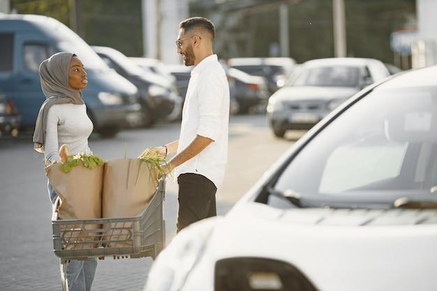Afrikanisches arabisches paar steht mit lebensmitteln in der nähe von elektroauto. elektroauto aufladen an der elektrotankstelle