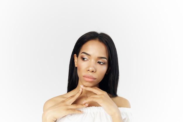 Afrikanisches aussehen der frau im weißen kleid, das kosmetikluxuslichthintergrund aufwirft