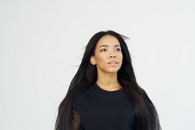 Afrikanisches aussehen der frau und langer dunkler haarkosmetiklichthintergrund