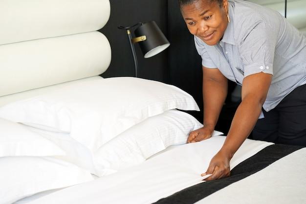Afrikanisches dienstmädchen, das bett im hotelzimmer macht. staff maid bett machen. afrikanische haushälterin macht bett.